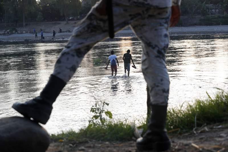 ARCHIVO - En esta fotografa del 22 de enero de 2020, unos migrantes hondureos que trataron de cruzar la frontera hacia Mxico a pie regresan al lado guatemalteco del ro Suchiate bajo la vigilancia de un elemento de la Guardia Nacional mexicana, cerca de Ciudad Hidalgo, Mxico. (AP Foto/Marco Ugarte, Archivo)