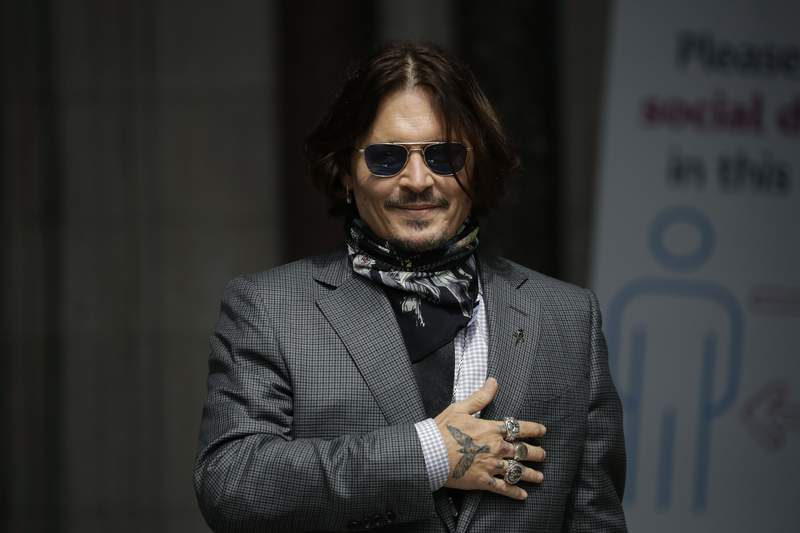 FILE - In this Thursday, July 23, 2020 file photo, U.S. actor Johnny Depp gestures to fans and the media as he arrives at the High Court in London. Spains most high-profile group of female filmmakers denounced the San Sebastian film festivals decision to award Johnny Depp its highest honor for acting on Monday Aug. 9, 2021. The move gives the festival a bad name after a British judge ruled allegations of domestic violence against Depp were substantially correct, it says. (AP Photo/Matt Dunham, file)