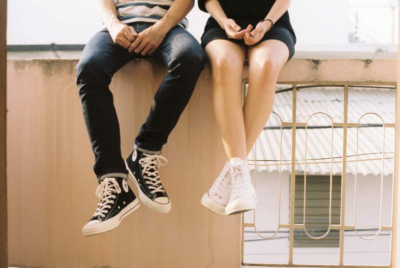A couple sits with their legs hanging.
