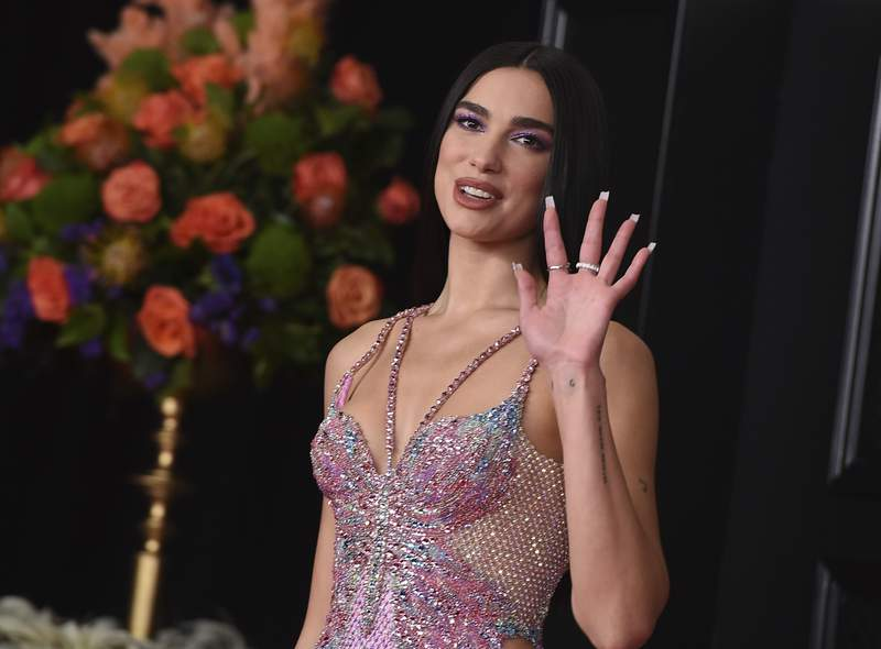 FILE - In this Sunday, March 14, 2021 file photo, Dua Lipa arrives at the 63rd annual Grammy Awards at the Los Angeles Convention Center. Singer Dua Lipa is blasting the organization which paid for a full-page ad in The New York Times that called her antisemitic for her support of Palestinians, saying it used her name shamelessly to advance their ugly campaign with falsehoods and blatant misrepresentations.  Lipa took to Twitter on Saturday, May 22, 2021 to reject the false and appalling allegations and said the World Values Network twisted what she stands for. I stand in solidarity with all oppressed people and reject all forms of racism, she wrote. (Photo by Jordan Strauss/Invision/AP, File)