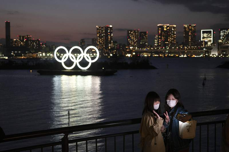 Two women take a selfie with the Olympic rings in the background in the Odaiba section of Tokyo, Thursday, March 12, 2020.  Doping testers around the sporting world are trying to avoid infecting themselves or athletes during the global virus outbreak, and that's not easy when collecting samples means getting very close to sports stars. (AP Photo/Jae C. Hong)