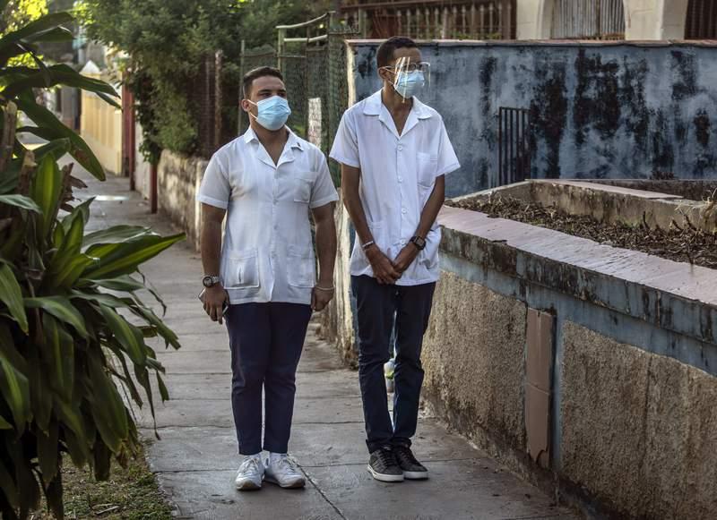 Dos estudiantes de medicina con mascarillas para protegerse del coronavirus escuchan respetuosamente el himno nacional en el Da del Trabajo, el 1 de mayo de 2021, en La Habana, Cuba. (AP Foto/Ramn Espinosa)