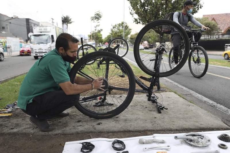 El venezolano Michael Ostis, de 33 aos, repara un bicicleta en Bogot, Colombia, el martes 9 de febrero de 2021. (AP Foto/Fernando Vergara)