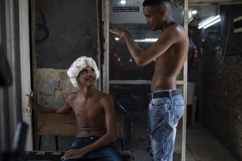 Unos residentes platican afuera de una barbera en la favela de Mandela, en Ro de Janeiro, Brasil, el sbado 27 de marzo de 2021. (AP Foto/Felipe Dana)