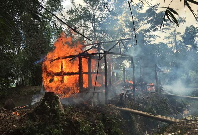 FILE - In this Sept. 7, 2017, file photo, houses are on fire in Gawdu Zara village, northern Rakhine state, Myanmar. Two soldiers who defected from Myanmars army and confessed on video to taking part in massacres, rape, and other crimes against the Muslim Rohingya minority are believed to be in the custody of the International Criminal Court in the Netherlands and should be prosecuted to obtain their evidence, a human rights organization said Tuesday. (AP Photo, File)