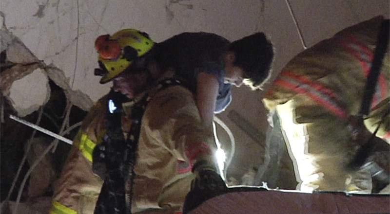 Imagen tomada de un video proporcionado por ReliableNewsMedia de bomberos rescatando a un sobreviviente del condominio Champlain despus de que se derrumbara parcialmente en Surfside, Florida, el jueves 24 de junio de 2021. (ReliableNewsMedia va AP)