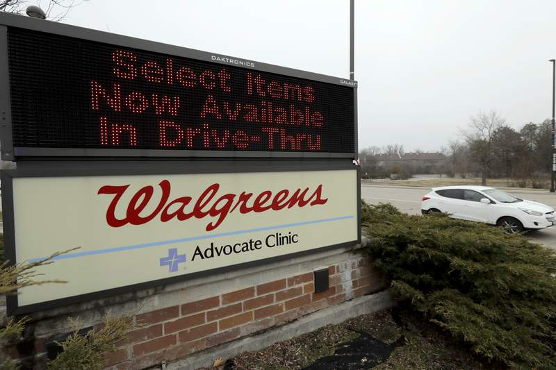 FILE - In this March 27, 2020, file photo, a Walgreens sign is displayed outside the store in Wheeling, Ill. Walgreens will hike starting pay to $15 an hour beginning in October, as employers across the United States continue boosting wages to attract workers. The drugstore chain said Tuesday, Aug. 31, 202, that the wage hike will take effect in phases and be completed by November 2022. (AP Photo/Nam Y. Huh, File)