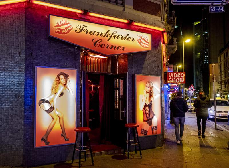 FILE - In this  Saturday, March 14, 2020 file photo people walk through the red light district in Frankfurt, Germany. The number of people registered as sex workers with German authorities declined sharply last year as coronavirus restrictions shut brothels for months, official data showed Thursday. (AP Photo/Michael Probst, file)