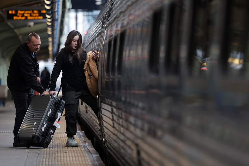 With the help of an Amtrak employee, a passenger brings her luggage onto a train. (Photo by Alex Wong/Getty Images)