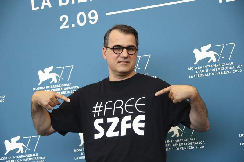 """Director Kornel Mundruczo poses for photographers at the photo call for the film 'Pieces of A Woman' during the 77th edition of the Venice Film Festival in Venice, Italy, Saturday, Sept. 5, 2020. He is wearing a t-shirt with the message """"Free SZFE,"""" a reference to a campaign protesting management changes at the University of Theatre and Film Arts (known by its acronym SZFE) imposed by the Victor Orban government that critics say will undermine the university's autonomy. (Photo by Joel C Ryan/Invision/AP)"""