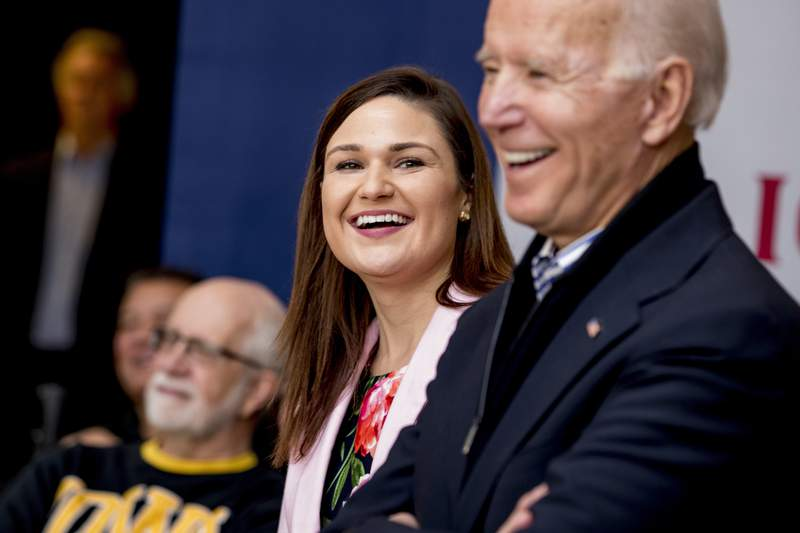 FILE - In this Friday, Jan. 3 2020 file photo, Democratic presidential candidate Joe Biden, right, and Rep. Abby Finkenauer, D-Iowa, center, smile during a campaign rally at the University of Dubuque, in Dubuque, Iowa. Iowa Democrat Abby Finkenauer is running for Republican Chuck Grassleys U.S. Senate seat. The one-term former congresswoman hopes her blue-collar credentials will propel her forward in a state that has grown more conservative over the years.  (AP Photo/Andrew Harnik)