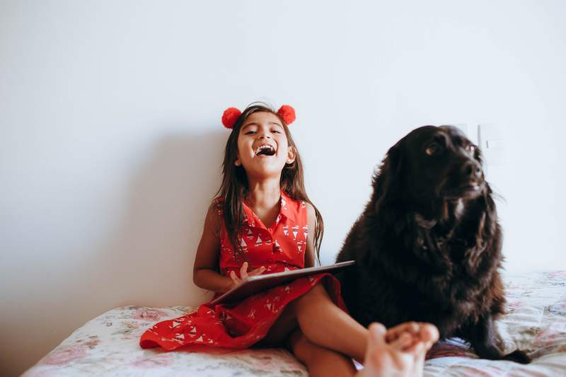 A girl plays on a tablet while her dog sits next to her.