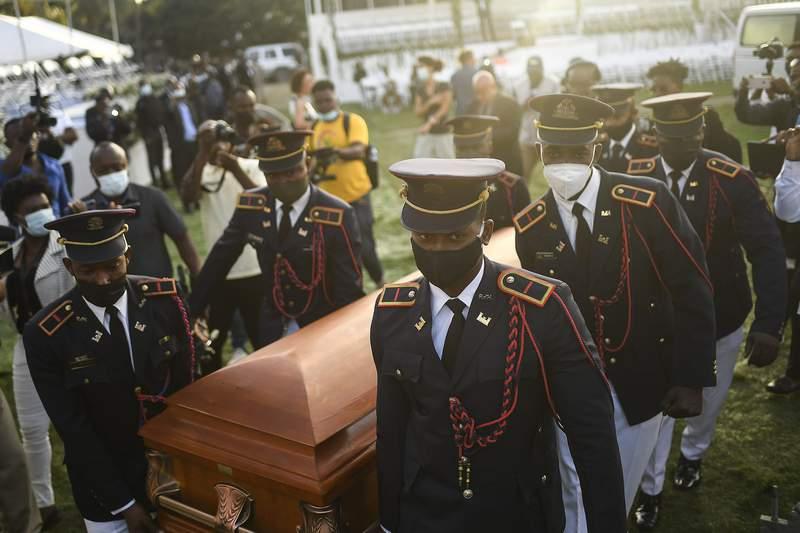 Policas cargan el fretro con los restos del presidente haitiano Jovenel Mose al inicio del funeral el viernes 23 de julio de 2021, en su finca familiar en Cabo Haitiano, Hait. (AP Foto/Matas Delacroix)