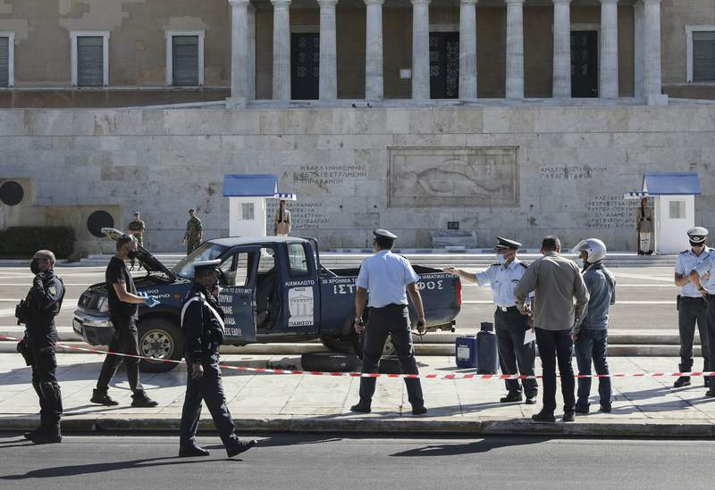 Police officers and bomb disposal officers check a pick up truck in front of the Greek Parliament in Athens , on Monday, Oct. 4, 2021. Police in Greece have halted traffic outside parliament in central Athens after a man drove a pickup truck onto a sidewalk in front of the building and reportedly threatened police. Bomb disposal officers checked the vehicle Monday and one cooking gas canister was removed. (John Liakos/InTime News via AP)