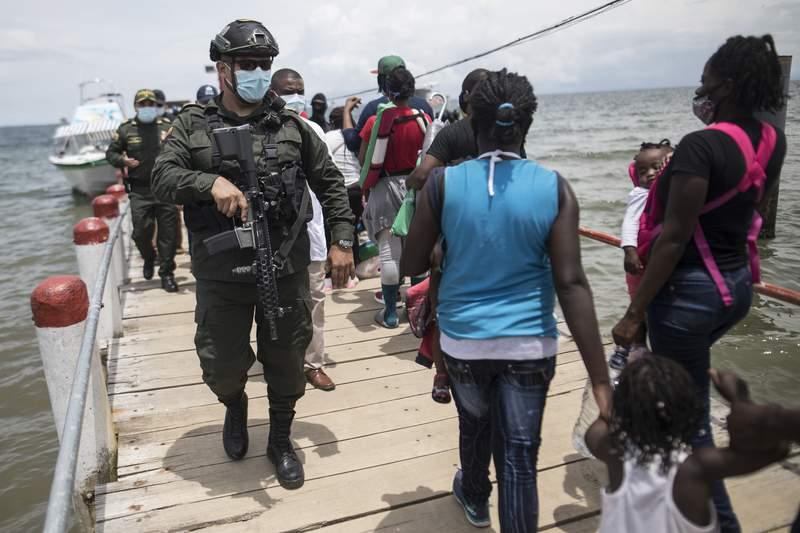 Varios policas caminan sobre el muelle el jueves 29 de julio de 2021 junto a migrantes que aguardan a abordar un bote que los llevar a Capurgana, en la frontera con Panam, desde Necocl, Colombia. (AP Foto/Ivn Valencia)