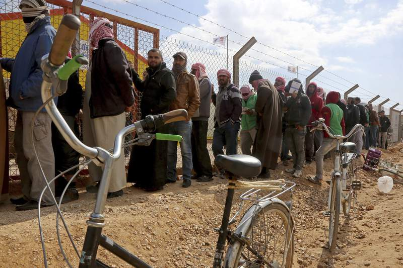 FILE - In this Feb. 18, 2018 file photo, Syrian refugees line up to register their names at an employment office, at the Azraq Refugee Camp, 100 kilometers (62 miles) east of Amman, Jordan. The U.N. agency for refugees said Tuesday, Sept. 8, 2020, that it has confirmed two coronavirus cases in the Azraq camp. They are the first infections to be detected among Syrians living in refugee camps in Jordan, which are home to more than 100,000 Syrians displaced by that country's civil war. (AP Photo/Raad Adayleh, File)