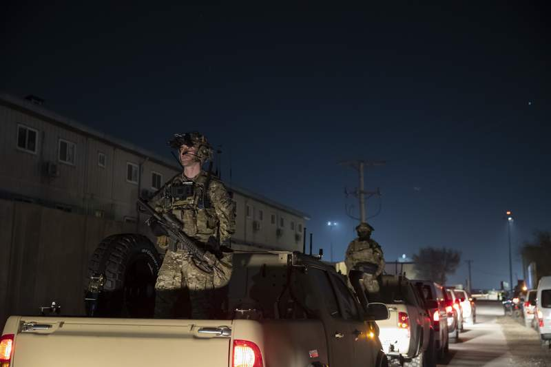FILE - In this Nov. 28, 2019, file photo armed soldiers stand guard in the motorcade for President Donald Trump speaks during a surprise Thanksgiving Day visit to the troops at Bagram Air Field, Afghanistan. Although the Islamic State extremist group is battered and scattered, it cannot be fully defeated until the world finds a way to reconcile and resettle the thousands of people displaced by years of war in Iraq and Syria, the general overseeing American military operations in the Mideast said Thursday, Nov. 19, 2020. (AP Photo/Alex Brandon, File)