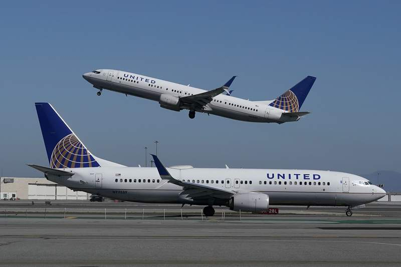 FILE - In this Oct. 15, 2020, file photo, a United Airlines airplane takes off over a plane on the runway at San Francisco International Airport in San Francisco. United Airlines says it will train 5,000 pilots at its own academy in this decade, and it hopes that half of them will be women or people of color. United said Tuesday, April 6, 2021, it is now taking applications for the academy in Arizona, including from people who have no flying experience.  (AP Photo/Jeff Chiu, File)