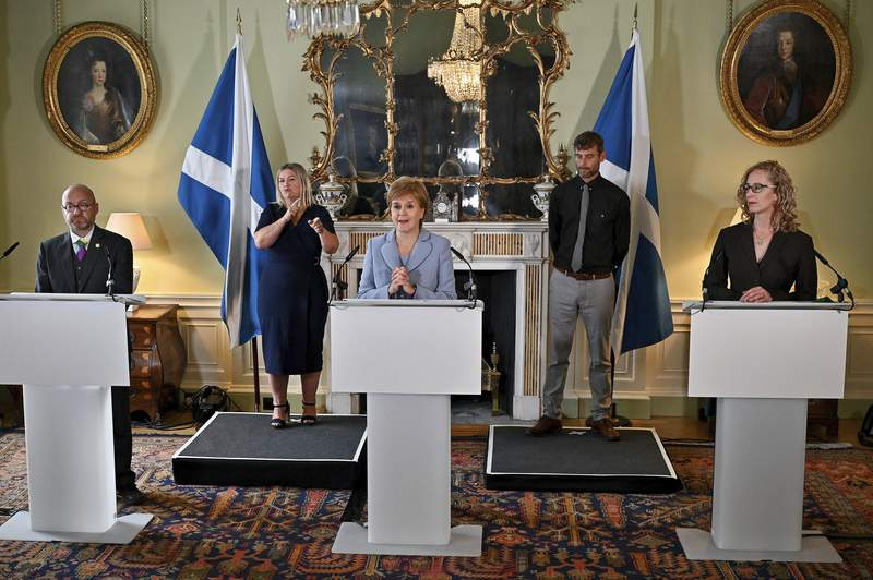 Scotland's First Minister Nicola Sturgeon, center, and Scottish Green Party co-leaders Patrick Harvie, left, and Lorna Slater speak to the media at Bute House, Edinburgh, Friday, Aug. 20, 2021. The Scottish National Party and the Scottish Greens have agreed a power-sharing deal that falls short of an official coalition government but could pave the way to another referendum on Scotlands independence from the U.K. in the coming couple of years. (Jeff J Mitchell/PA via AP)