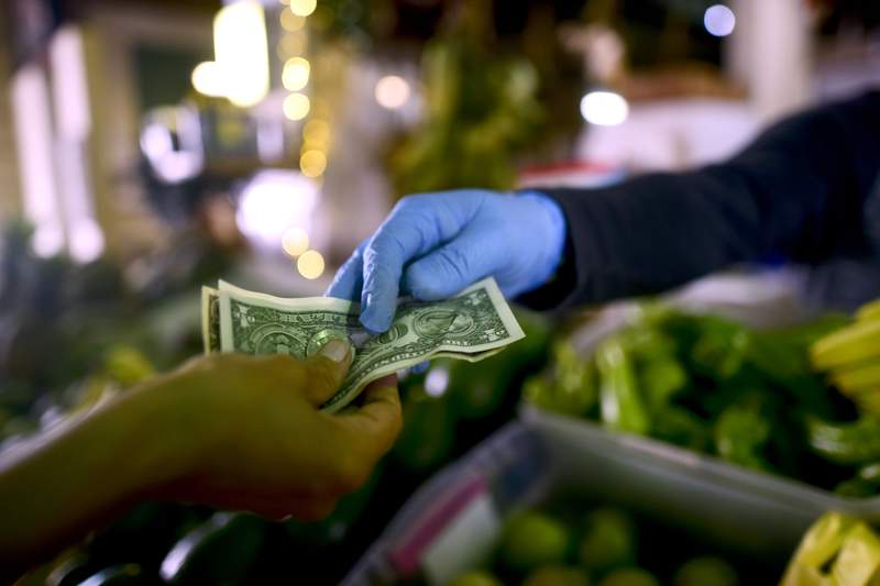 FILE - In this March 19, 2020, file photo, Jorge Otero, owner of a fruit and vegetables stand, wears gloves as he exchanges cash with a customer, during a government curfew aimed at curbing cases of the new coronavirus in San Juan, Puerto Rico. From the supermarkets of the United States and Japan to the shantytowns of Africa to the gas stations of Tehran, a growing number of businesses and individuals worldwide have stopped using banknotes in fear that physical currency, handled by tens of thousands of people over their useful life, could be a vector for the spreading coronavirus. (AP Photo/Carlos Giusti)