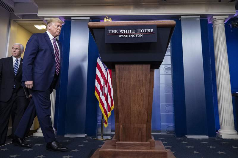 President Donald Trump, followed by Vice President Mike Pence, arrives to speak about the coronavirus in the James Brady Press Briefing Room of the White House, Friday, April 24, 2020, in Washington. (AP Photo/Alex Brandon)
