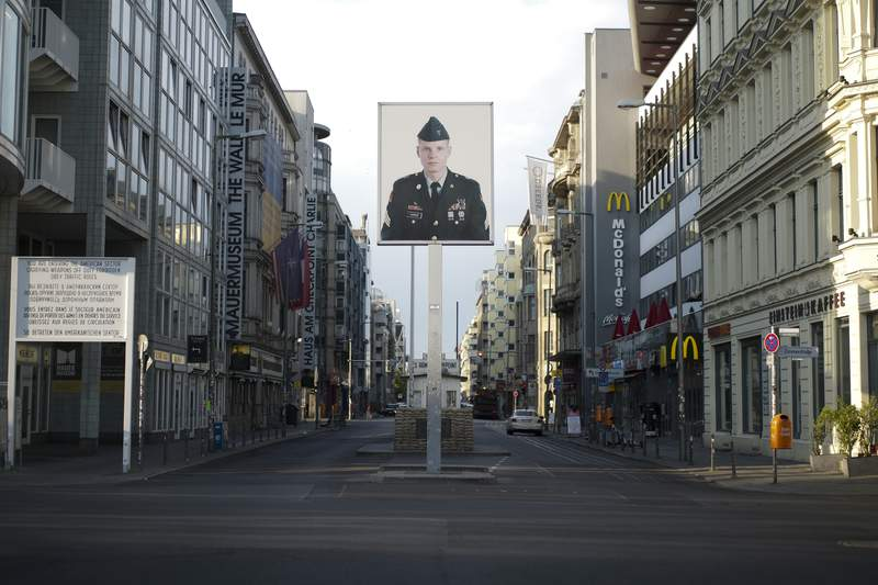 FILE - In this June 9, 2020, file photo, a picture of a former American soldier is displayed at the former U.S. army Checkpoint Charlie in Berlin, Germany. In vowing to pull thousands of U.S. troops from Germany, President Donald Trump is following a pattern of disruptive moves against allies that have dismayed many of his fellow Republicans. Trump has consistently promised to bring American troops home, dismissing the conventional view that a far-flung U.S. military presence, while costly, pays off in the long run by ensuring stability for global trade. Earlier this week he said the 34,500 U.S. troops in Germany would be reduced to 25,000. (AP Photo/Markus Schreiber, File)