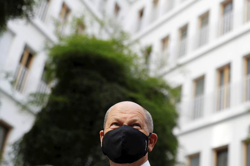 German Finance Minister Olaf Scholz wearing a protective mask arrives for a news conference to present the federal government's 2021 draft budget and its longer-term spending plans, amid the coronavirus disease (COVID-19) outbreak, in Berlin, Germany, Wednesday, Sept. 23, 2020. (Fabrizio Bensch/Pool via AP)