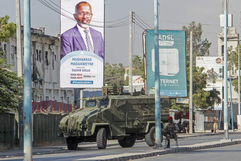 Security forces block a street with an armored personnel carrier during protests against the government and the delay of the country's election in the capital Mogadishu, Somalia Friday, Feb. 19, 2021.  Security forces in Somalia's capital fired on hundreds of people protesting the delay of the country's election on Friday as at least one explosion was reported at the international airport and armored personnel carriers blocked major streets. (AP Photo)