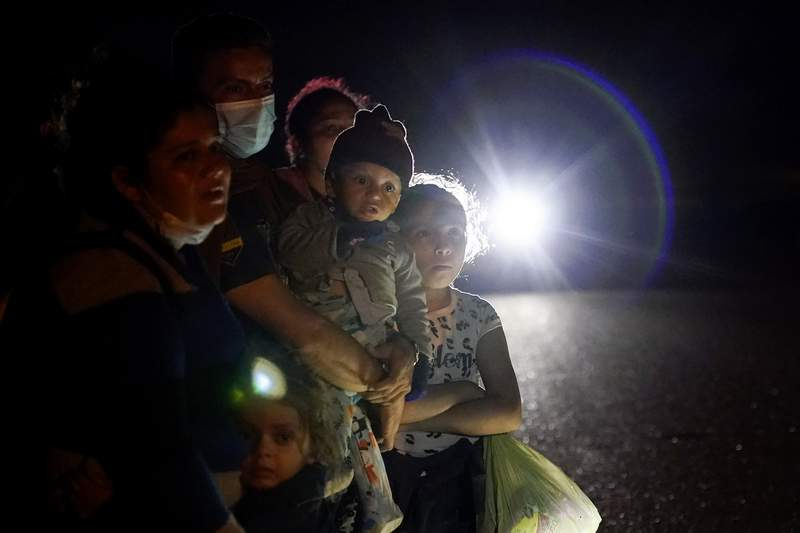 ARCHIVO - En esta fotografa del 17 de mayo de 2021 se muestra un grupo de migrantes procedentes de Honduras y Nicaragua que esperan en un camino luego de que se entregaron a las autoridades en La Joya, Texas. (AP Foto/Gregory Bull, Archivo)
