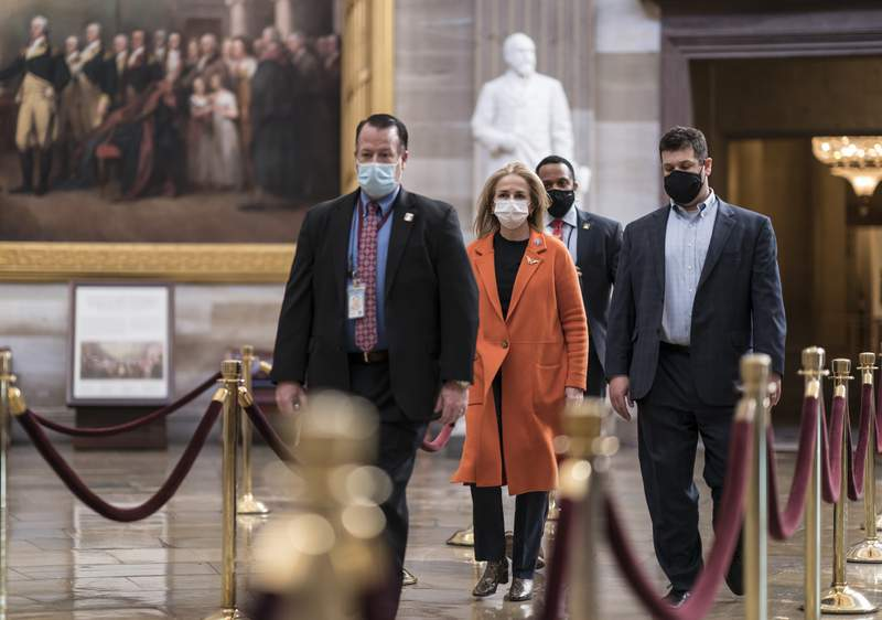 On the eve of the second impeachment trial of former President Donald Trump, Rep. Madeleine Dean, D-Pa., one of the Democratic House impeachment managers, is escorted by security through the Rotunda after preparing for the case in the Senate, at the Capitol in Washington, Monday, Feb. 8, 2021. The trial will begin Tuesday with a debate and vote on whether it's even constitutional to prosecute the former president, an argument that could resonate with Republicans keen on voting to acquit Trump. (AP Photo/J. Scott Applewhite)