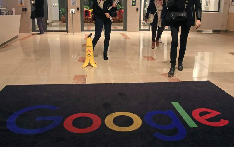 FILE - In this file photo dated Nov. 18, 2019, Google employees walk out of Google France building in Paris. Frances competition regulator said Tuesday, July 13, 2021 it fined Google 500 million euros ($592 million) for failing to negotiate in good faith with French publishers in a dispute over payments for their news. (AP Photo/Michel Euler, File)