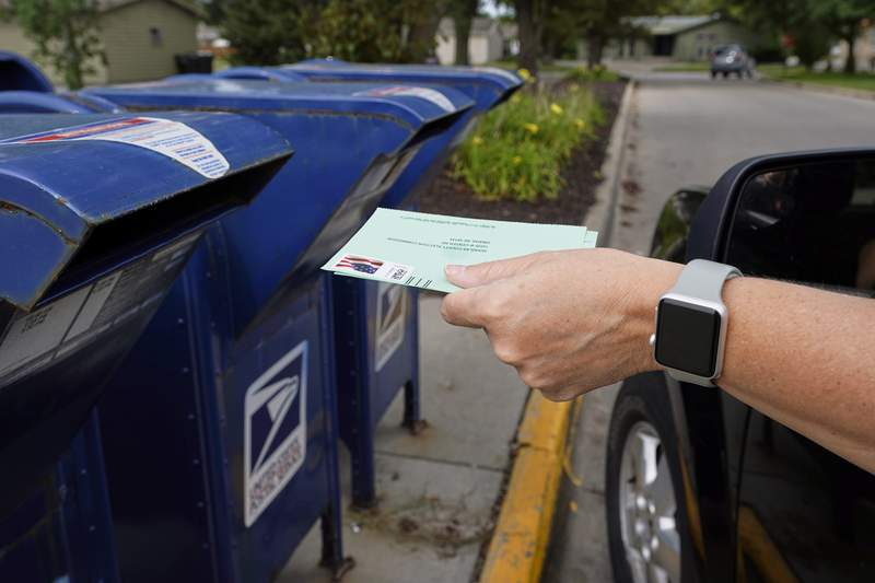 """FILE - In this Tuesday, Aug. 18, 2020, file photo, a person drops applications for mail-in-ballots into a mail box in Omaha, Neb. A U.S. judge on Thursday, Sept. 17, 2020, blocked controversial Postal Service changes that have slowed mail nationwide. The judge called them """"a politically motivated attack on the efficiency of the Postal Service"""" before the November election. (AP Photo/Nati Harnik, File)"""