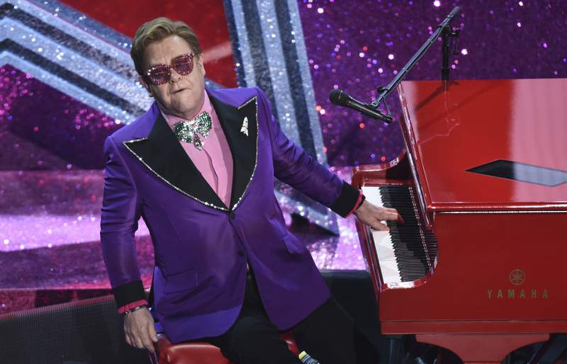 """FILE - In this Sunday, Feb. 9, 2020 file photo, Elton John performs """"(I'm Gonna) Love Me Again"""" nominated for the award for best original song from """"Rocketman"""" at the Oscars, at the Dolby Theatre in Los Angeles. Elton John says he is postponing European dates on his world tour until 2023 so that he can have an operation on an injured hip. The 74-year-old singer-songwriter had been due to play cities in Britain and Europe this year. (AP Photo/Chris Pizzello, File)"""