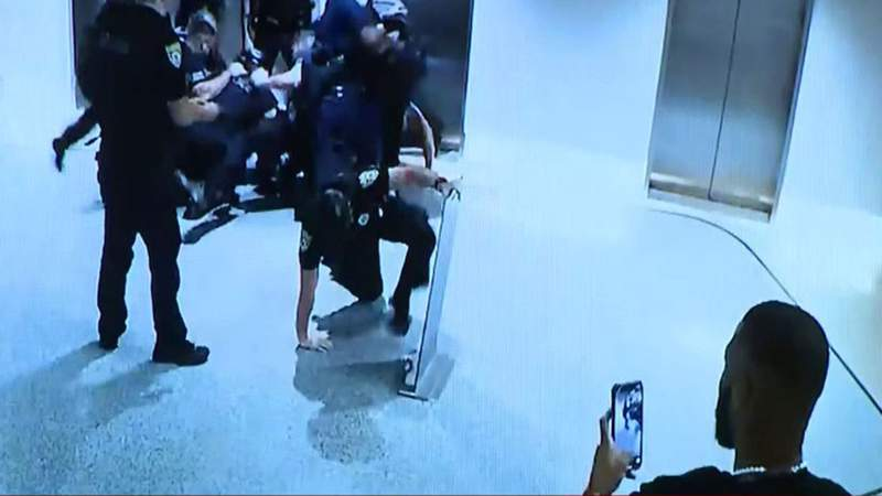 Khalid Vaughn uses his phone to film police officers during a July 26 arrest in the lobby of the Royal Palm Hotel in Miami Beach.
