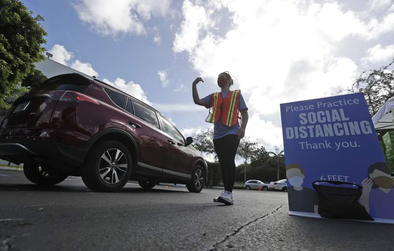 Cars are welcomed in for a food drive distribution in Miami in this file photo.