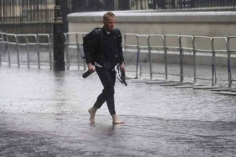Un hombre camina descalzo por unas inundaciones en el centro de Londres, el domingo 25 de julio de 2021. (Victoria Jones/PA va AP)