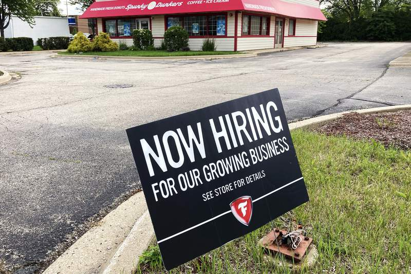 A hiring sign is displayed at Firestone Complete Auto Care store in Arlington Heights, Ill., Wednesday, June 30, 2021.  The U.S. job market is storming into summer: Job creation and wages rose sharply in June, and more and more Americans are confident enough to quit their jobs and look for something better. The Labor Department reported Friday, July 2 that employers added 850,000 jobs last month, most since August.(AP Photo/Nam Y. Huh)