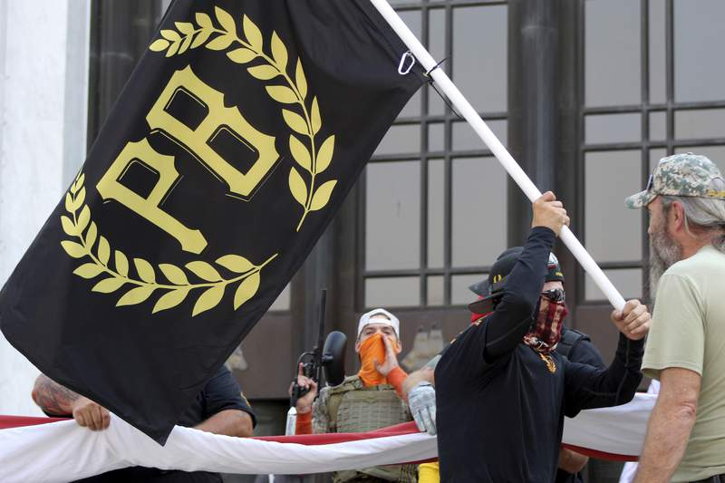 FILE - In this Sept. 7, 2020, file photo, a protester carries a Proud Boys banner, a right-wing group, while other members start to unfurl a large U.S. flag in front of the Oregon State Capitol in Salem, Ore.  The Canadian government designated the Proud Boys group as a terrorist entity on Wednesday, Feb. 3, 2021, noting they played a pivotal role in the insurrection at the U.S. Capitol on Jan. 6.  (AP Photo/Andrew Selsky, File)