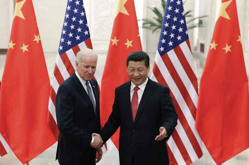 FILE - In this Dec. 4, 2013, file photo, Chinese President Xi Jinping, right, shakes hands with then U.S. Vice President Joe Biden as they pose for photos at the Great Hall of the People in Beijing. (AP Photo/Lintao Zhang, Pool, File)