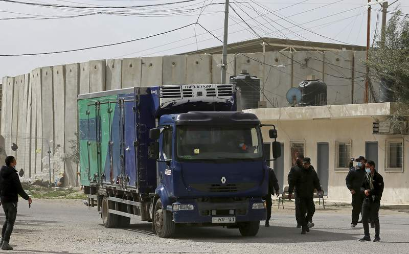 Hamas police officers guard a truck containing a shipment of Russian Sputnik V coronavirus vaccines at the Kerem Shalom border crossing, in Rafah, Gaza Strip, Wednesday, Feb. 17, 2021. The Palestinian Authority said Wednesday that it dispatched the first shipment of coronavirus vaccines to the Hamas-ruled Gaza Strip, two days after accusing Israel of preventing it from sending the doses amid objections from some Israeli lawmakers. (AP Photo/Adel Hana)