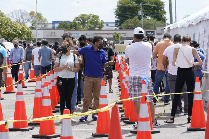 People wait in line to receive a COVID-19 vaccine at a FEMA vaccination center at Miami Dade College on April 5. Any adult in Florida is now eligible to receive the coronavirus vaccine. In addition, the state announced that teens ages 16 and 17 can also get the Pfizer vaccine with parental permission.
