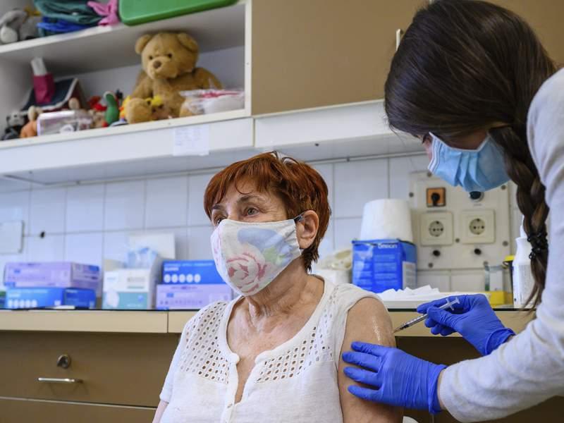 A health worker administers a dose of Pfizer-BioNtech vaccine against the new coronavirus to a patient at Szent Gyorgy Training Hospital in Szekesfehervar, Hungary, Monday, April 19, 2021. (Tamas Vasvari/MTI via AP)