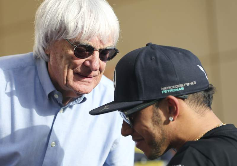 FILE - In this Thursday, April 16, 2015 file photo, Bernie Ecclestone, President and CEO of Formula One Management, left, talks to Mercedes driver Lewis Hamilton of Britain ahead the Bahrain Formula One Grand Prix at the Formula One Bahrain International Circuit in Sakhir, Bahrain. Formula One champion Lewis Hamilton has criticized ignorant and uneducated comments by former F1 boss Bernie Ecclestone. Hamilton, a six-time world champion and the only Black driver in F1, was shocked by Ecclestone's claim during an interview with broadcaster CNN on Friday, June 26, 202 that in lots of cases, Black people are more racist than white people. (AP Photo/Kamran Jebreili, File)