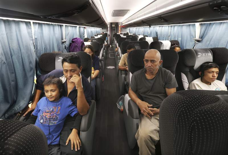 FILE - In this July 18, 2019 file photo, migrants sit in a bus that was organized by the Mexican government, which will take them from an immigration center in the border city of Nuevo Laredo to Monterrey, Mexico, after they were returned to Mexico by U.S. authorities. (AP Photo/Marco Ugarte, File)