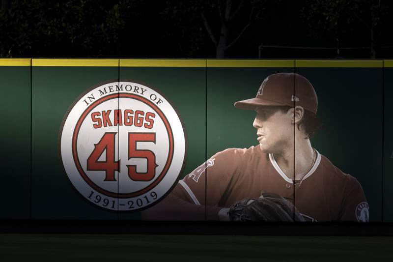 FILE - In this July 17, 2019, file photo, an image and logo for memorializing former Los Angeles Angels pitcher Tyler Skaggs is displayed on the outfield wall in Anaheim, Calif.  A federal grand jury on Thursday, Oct. 15, 2020, has indicted Eric Prescott Kay, a former Los Angeles Angels employee in the death of Angels pitcher Tyler Skaggs from the drugs Kay is accused of providing. (AP Photo/Kyusung Gong, File)
