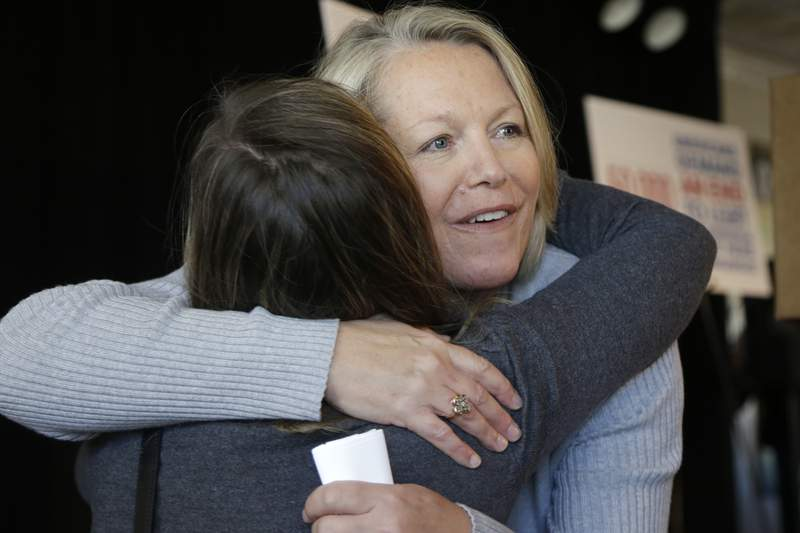 """FILE - in this Oct. 22, 2013 file photo, Mount St. Mary school teacher then, Tippi McCullough, right, is hugged by a supporter after a Little Rock, Ark. The Catholic school teacher was allegedly told she would be fired from her job after she married her wife in New Mexico. A longtime abortion opponent who once opposed allowing gay couples to be foster parents, Arkansas Gov. Asa Hutchinson is the unlikeliest figure to complain about bills on the """"culture wars"""" reaching his desk.But by vetoing a ban on gender confirming treatments for transgender youth, the Republican offered a rare rebuke to fellow conservatives who have been in overdrive this legislative session with bills targeting LGBTQ people, restricting abortionaccessand expanding gun rights. (AP Photo/Danny Johnston File)"""