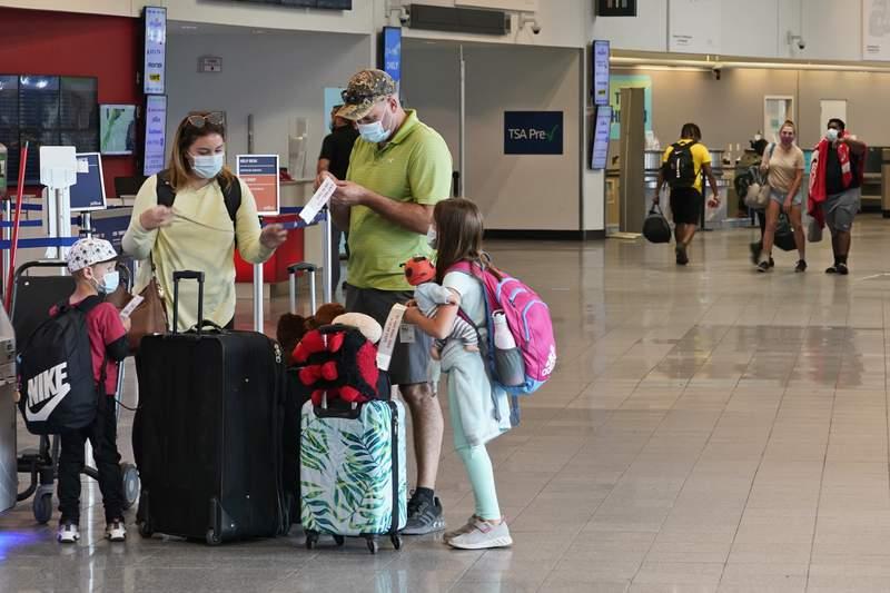 ARCHIVO - En esta foto del 26 de mayo del 2021, una familia se prepara para registrar su equipaje en el Aeropuerto Internacional Hopkins, en Cleveland. Ms de 1,8 millones de personas pasaron por los aeropuertos estadounidenses el jueves, 28 de mayo, y se espera que la cifra supere los dos millones durante el fin de semana del feriado por los Cados en Guerras _ lo que sera el mayor nivel desde inicios de marzo del 2020. (AP Foto/Tony Dejak)