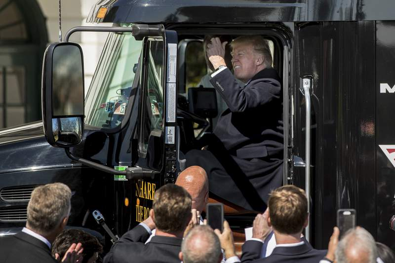FILE - In this March 23, 2017, file photo President Donald Trump honks the horn of an 18-wheeler truck while meeting with truckers and CEOs regarding healthcare on the South Lawn of the White House in Washington. Trump publicly acknowledged that humans bear some blame for climate change, but scientists say the president still isn't dealing with the reality of our primary role. Trump said Tuesday, Sept. 29, 2020, that humans  their tailpipe exhaust, oil and gas production, and smokestack fumes  are just one of many culprits for the weather-disrupting deterioration of Earths atmosphere. (AP Photo/Andrew Harnik, File)
