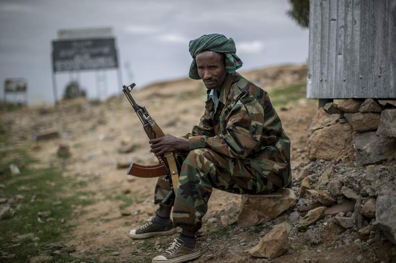 """FILE - In this Friday, May 7, 2021 file photo, a fighter loyal to the Tigray People's Liberation Front (TPLF) mans a guard post on the outskirts of the town of Hawzen, then-controlled by the group but later re-taken by government forces, in the Tigray region of northern Ethiopia. Ethiopias spreading Tigray conflict faces a fresh wave of fighting as an Amhara regional official says Amhara forces will launch an offensive on Saturday, Aug. 7, 2021 against Tigray forces who have entered the region and taken control of a town hosting a UNESCO World Heritage Site. The Amhara regions head of peace and security says this is the time for the Amhara people to crush the terrorist group. Separately, Ethiopias foreign ministry warns that the Tigray forces incursion into the Amhara and Afar regions in recent weeks is testing the federal governments patience"""" on the unilateral cease-fire it declared weeks ago. (AP Photo/Ben Curtis, File)"""