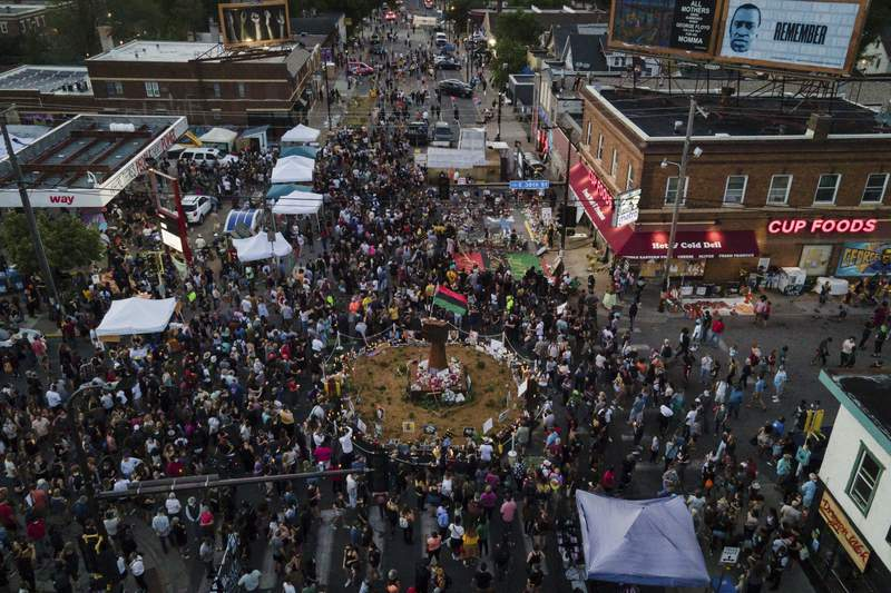 In a photo taken with a drone, people gather at George Floyd Square on the one-year anniversary of Floyd's death, Tuesday, May 25, 2021, in Minneapolis. (AP Photo/Christian Monterrosa)